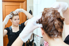 Pelos de teñido de la hembra en el cuarto de baño doméstico Fotografía de archivo libre de regalías