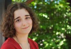 Pelos marrones rizados de la mujer joven en un parque Imagen de archivo