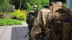 Pelotón de los guerreros de la guerrilla que camina en la línea formación que lleva sus armas en el ambiente urbano metrajes