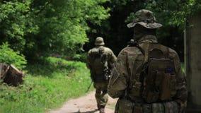 Pelotón de los guerreros de la guerrilla que camina en la línea formación que lleva sus armas en el ambiente urbano almacen de video