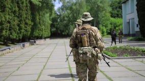 Pelotón de los guerreros de la guerrilla que camina en la línea formación que lleva sus armas en el ambiente urbano almacen de metraje de vídeo