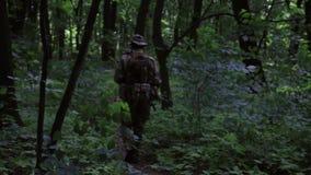 Pelotón de los guerreros de la guerrilla que corre en una formación que lleva sus armas en los arbustos del bosque metrajes