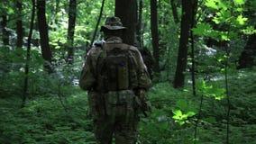 Pelotón de los guerreros de la guerrilla que corre en una formación que lleva sus armas en los arbustos del bosque almacen de video