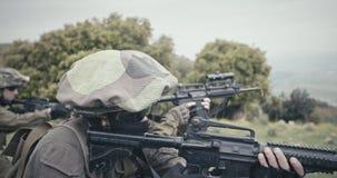 Pelotón de soldados completamente armados del comando durante combate en un paisaje del bosque almacen de video