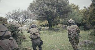 Pelot?n de soldados completamente armados del comando durante combate en un paisaje del bosque almacen de video