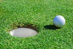 Pelota de golf al lado de la taza con la profundidad del campo baja Fotografía de archivo