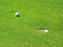 Pelota de golf al lado del agujero Fotos de archivo