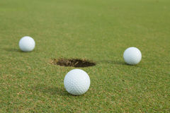 pelota de golf 3 al lado del agujero Imágenes de archivo libres de regalías
