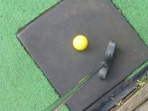 Pelota de golf amarilla con el putter Fotos de archivo