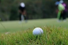 Pelota de golf borrosa en verde en el campo de golf de la tarde con el sunsh Imagenes de archivo
