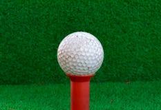 Pelota de golf, camiseta en el fondo de la hierba de la falta de definición Imagen de archivo