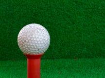 Pelota de golf, camiseta en el fondo de la hierba de la falta de definición Fotografía de archivo
