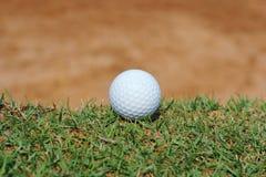 pelota de golf cerca de la arcón de la arena Fotos de archivo libres de regalías