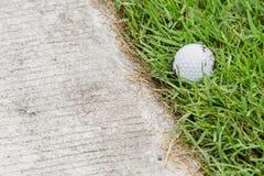 Pelota de golf cerca de la trayectoria del carro Fotos de archivo