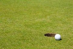 Pelota de golf cerca de un agujero Imágenes de archivo libres de regalías