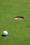 Pelota de golf cerca del agujero Imagen de archivo libre de regalías