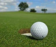 Pelota de golf cerca del agujero Fotografía de archivo