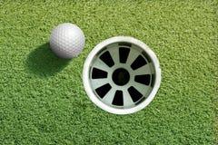 Pelota de golf cerca del agujero Fotografía de archivo libre de regalías