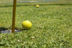 Pelota de golf cerca del agujero Imagen de archivo