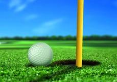 Pelota de golf cerca del agujero Fotos de archivo libres de regalías