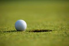 Pelota de golf cerca del agujero Imágenes de archivo libres de regalías