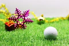 Pelota de golf con la decoración de la Navidad para el día de fiesta del golfista Fotos de archivo