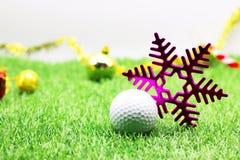 Pelota de golf con la decoración de la Navidad para el día de fiesta del golfista Foto de archivo libre de regalías
