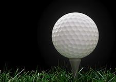 Pelota de golf con la te en la hierba Imagen de archivo