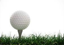 Pelota de golf con la te en la hierba Foto de archivo