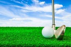 Pelota de golf e hierro en hierba verde artificial Fotos de archivo