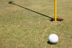 Pelota de golf e indicador en agujero Imágenes de archivo libres de regalías