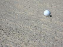 Pelota de golf en arcón de la arena Fotos de archivo