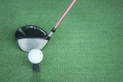 Pelota de golf en camiseta con el club del conductor, delante del conductor, campo de prácticas Imagen de archivo libre de regalías