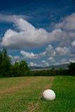 Pelota de golf en curso y el cielo azul Fotografía de archivo libre de regalías