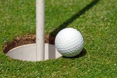 Pelota de golf en el agujero Fotografía de archivo