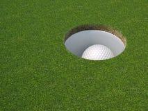 Pelota de golf en el agujero Imagenes de archivo