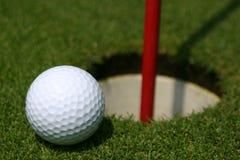 Pelota de golf en el agujero de la práctica Foto de archivo libre de regalías