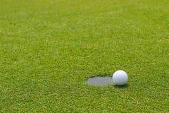 Pelota de golf en el borde de poner el control de la taza en el putting green fotos de archivo