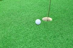 Pelota de golf en el labio de la taza Fotos de archivo libres de regalías