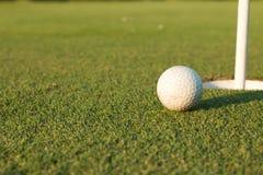 Pelota de golf en el labio de la taza Imágenes de archivo libres de regalías