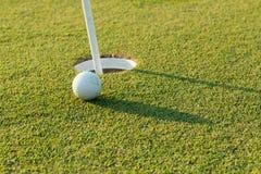 Pelota de golf en el labio de la taza Foto de archivo libre de regalías