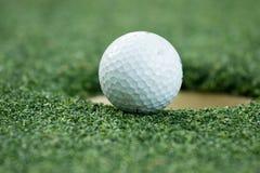 Pelota de golf en el labio de la taza Fotografía de archivo libre de regalías