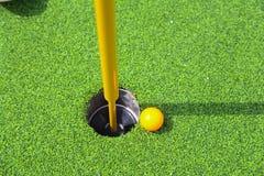 Pelota de golf en el labio de la taza foto de archivo