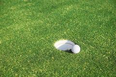 Pelota de golf en el labio de la taza imagen de archivo