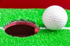 Pelota de golf en el labio de la taza, concepto de la meta foto de archivo