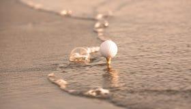 Pelota de golf en el mar imagen de archivo