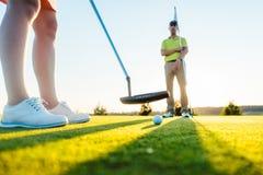 Pelota de golf en foco selectivo debajo del club del putter de un jugador femenino Imagenes de archivo