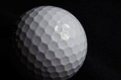 Pelota de golf en fondo negro Fotos de archivo libres de regalías