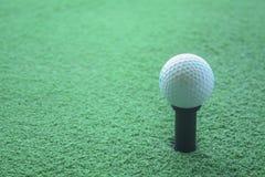 Pelota de golf en la camiseta lista para ser tirado en un drivingrange Imagen de archivo