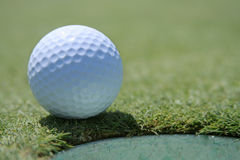 Pelota de golf en la taza Imagenes de archivo
